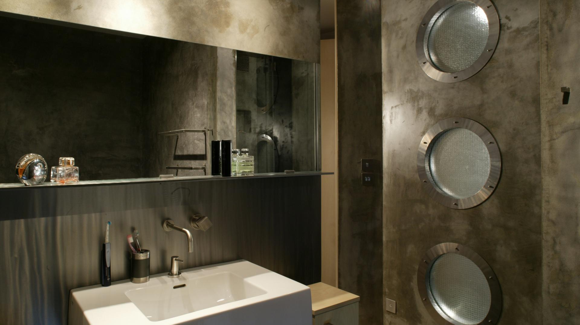 Otoczenie misy umywalki sprawia ascetyczne wrażenie. Zarówno ścienna bateria, jak i lustro z linią szklanej półki nad nią reprezentują minimalistyczne wzornictwo. Fot. Tomasz Markowski.