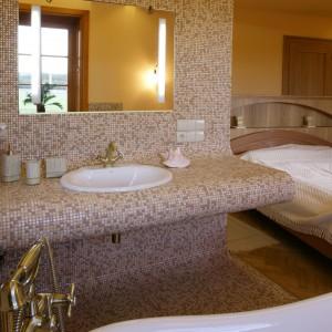 Niepełnej wysokości ścianka oddziela część kąpielowo-toaletową od natrysku. Jej łagodnie zarysowane linie, bez kątów prostych, dają wrażenie przytulności. Fot. Monika Filipiuk.