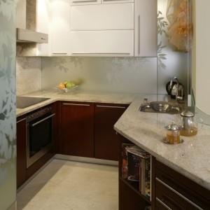 Robocza część kuchni jest naprawdę  niewielka. Wizualnej przestronności dodają jej lustrzane tafle umieszczone wokół wiszących szafek. Wypiaskowane na niej motywy dekorują i intrygują zarazem.