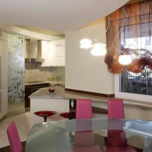 Forma szklanego stołu jadalnianego jest lustrzanym odbiciem kształtu podwieszonego sufitu. Ażurowa konstrukcja lampionów przydaje lekkości całej kompozycji, a okno użycza stołownikom naturalnego światła.