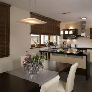 Kontrastowe zestawienie barw w kuchennej zabudowie ma swoją kontynuację w jadalni. Ciemny dębowy stół otaczają krzesła w kremowej tapicerce. Fot. Monika Filipiuk.