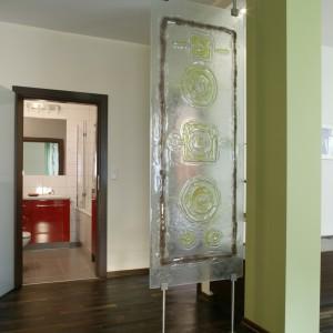 Wejście do łazienki od dziennej strefy mieszkania dyskretnie przesłania tafla szkła typu fusing. Zawieszona została na stalowych prętach między podłogą a sufitem. Fot. Monika Filipiuk.