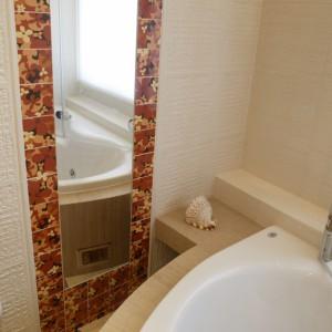 Pionowa tafla lustra w sąsiedztwie wanny optycznie powiększa wąską łazienkę. Ujęta w ramy z kolorowych płytek daje ciekawy, przyciągający uwagę efekt. Fot. Monika Filipiuk.