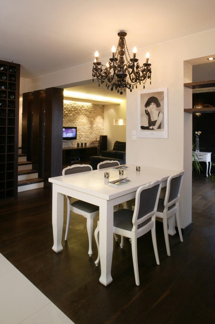 Wyrazistość na dzień dobry, kompozycja idealna: na prawie czarnej podłodze (dąb olejowany) stanął kontrastujący z nią jasny zestaw jadalniany, złożony ze stołu i krzeseł o klasycznych kształtach. Fot. Monika Filipiuk.