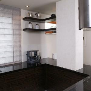 Kuchnia jest prosta, nowoczesna i funkcjonalna. Zastosowano tu głównie fornir hebanowy, szkło i czarny kamień. Fot. Monika Filipiuk.