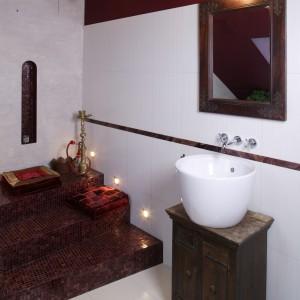 Umywalka w kształcie głębokiej misy ustawiona została na nietypowym postumencie – stylowej drewnianej szafce idealnie wpisującej się w orientalny klimat wnętrza. Fot. Monika Filipiuk.