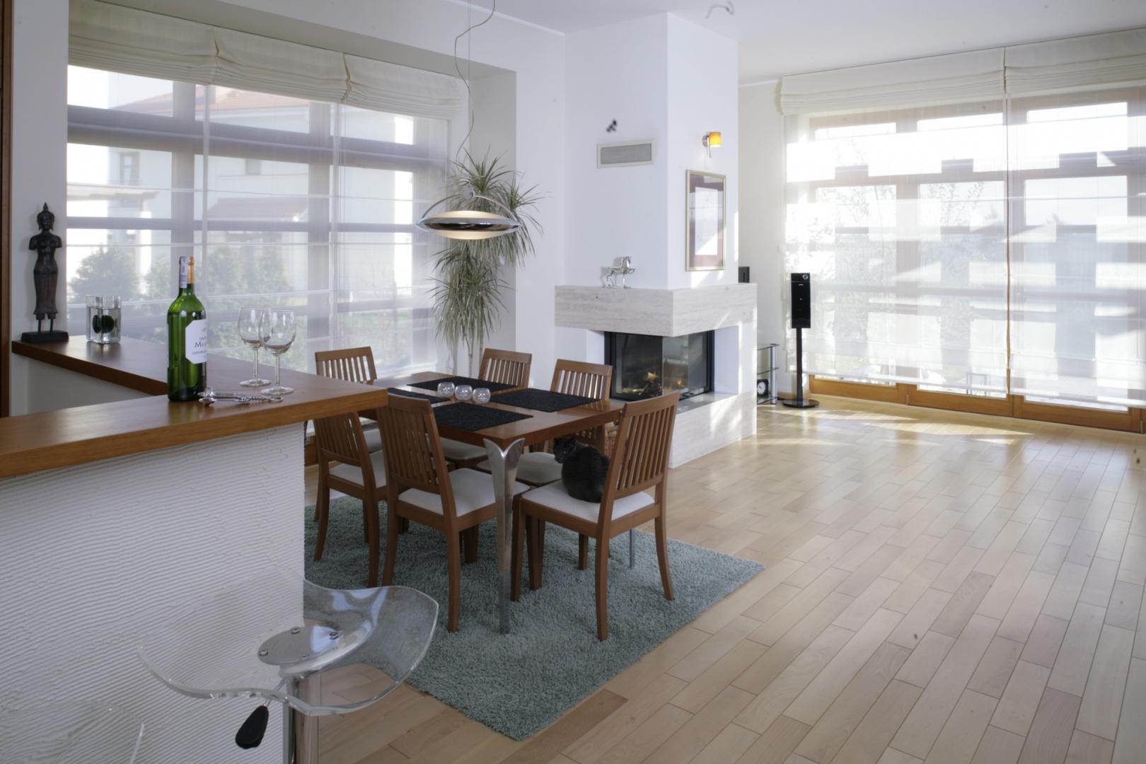 Ogromne okna sprawiają, że wnętrze jest bardzo jasne i przestronne. Światło dzienne pada na stół jadalniany (BoConcept) ustawiony nieopodal jednego z nich. Krzesła (BoConcept) w tej strefie okazały się bardzo wygodnym posłaniem dla Kocura Księcia. Fot. Monika Filipiuk.