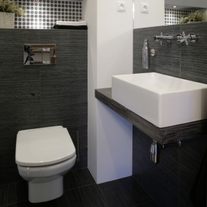 W niewielkiej łazience dla gości, zlokalizowanej nieopodal schodów, panuje kolorystyka metalicznej szarości. Barwę tę mają płytki, którymi wyłożono podłogę i ściany do poziomu luster. Fot. Monika Filipiuk.