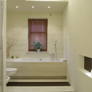 """Na pierwszy rzut oka widać, że ta łazienka jest łazienką małżeńską. Jasne kolory, ozdoby w postaci zasuszonych gałązek na wannie – oczywiste atrybuty kobiece, przeplatają się z """"męskimi"""" akcentami czekoladowego brązu. Fot. Monika Filipiuk."""