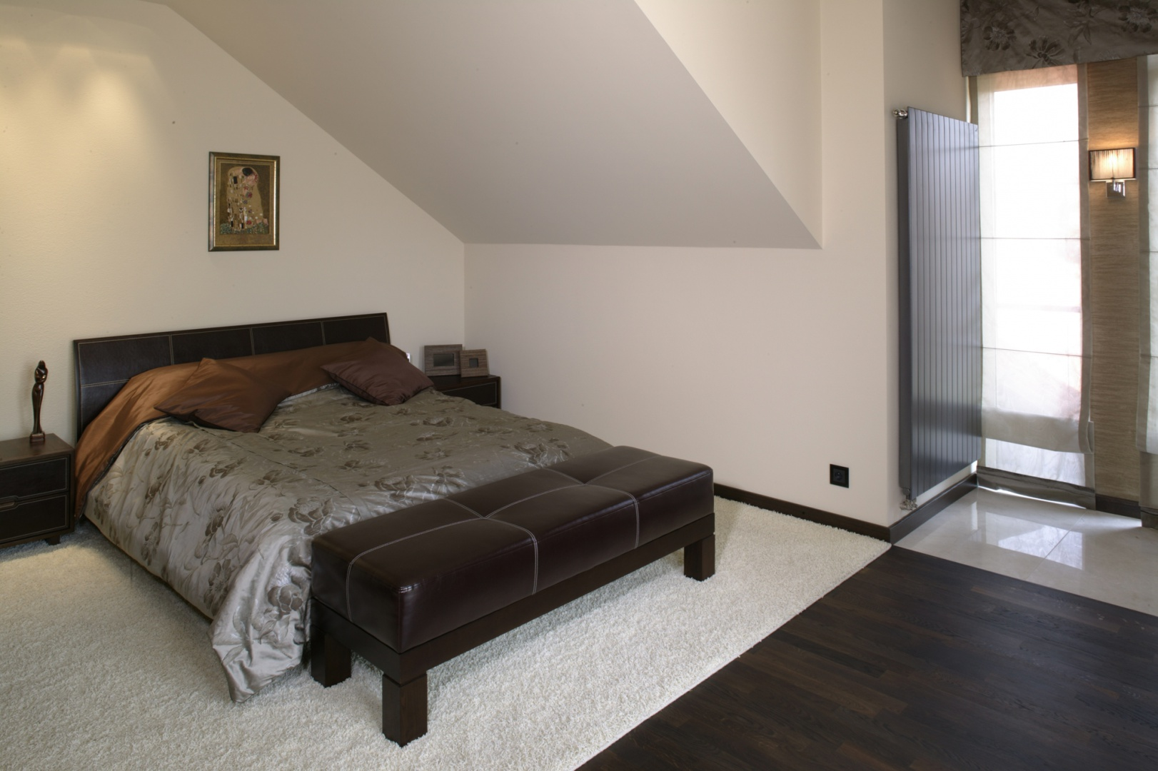 """Sypialnia to kolorystyczna oaza spokoju – bezpieczna i stonowana """"kawa ze śmietanką"""". Solidne, eleganckie meble, będące połączeniem drewna wenge i skóry, kontrastują z białym dywanem i jasnymi ścianami. Fot. Monika Filipiuk."""