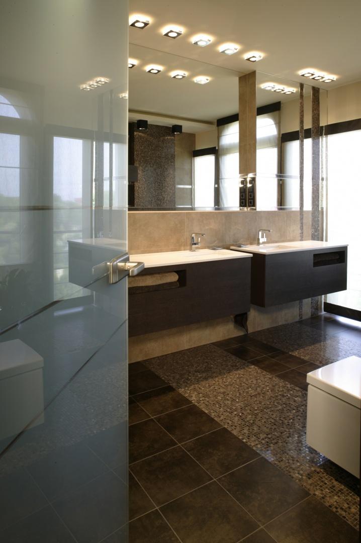 Utrzymana w odcieniach beżów i brązów łazienka jest nowoczesna i efektowna. Ogromne okna i tafle luster dodają jej przestrzeni i wizualnej lekkości. Fot. Monika Filipiuk.