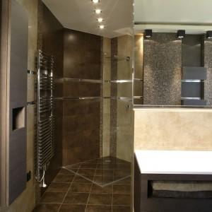 Schowana w kącie, szklana kabina prysznicowa, została tak wtopiona w kamienne tło, że jest prawie niewidoczna. Uwagę zwraca hiszpański komplet łazienkowych mebli z wenge, o interesującym designie. Fot. Monika Filipiuk.