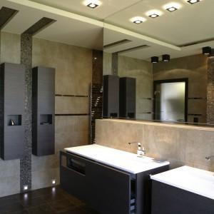 Ścianka z umywalkami osłania wannę i częściowo kabinę prysznicową. Szafki – wąskie, wiszące i podumywalkowe – mają proste, interesujące wzornictwo. Fot. Monika Filipiuk.