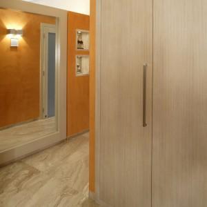 Ściany w przedpokoju zostały pokryte dekoracyjnym stiukiem w pomarańczowym kolorze (Oikos), a podłoga – delikatnie połyskującym marmurem breccia sarda. Wysoką szafę i wszelkie elementy drewniane wykonano z bielonego dębu. Fot. Monika Filipiuk.