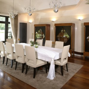 W salonie wydzielono jeszcze jedną strefę – przestronną elegancką jadalnię. W jej sercu ustawiono duży stół z kompletem krzeseł (Selva). Do stylowych witryn Selvy (idealne miejsce na piękną zastawę stołową) architekt specjalnie zaprojektowała ścianę ekspozycyjną. Fot. Monika Filipiuk.