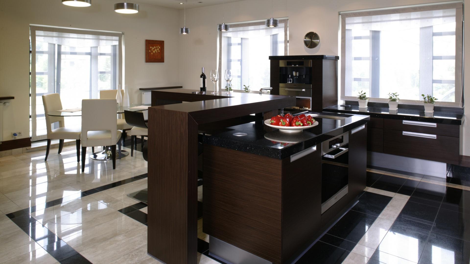 W kuchni mamy smakowitą grę odcieni czekolady i kremu. Meble w fornirze wengé (A-Z Kuchnia) kontrastują z marmurowymi fragmentami podłogi. Fot. Monika Filipiuk.