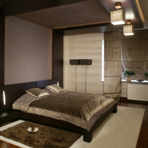 Drewno wengé, z którego został wykonany nie tylko ten główny, sypialniany mebel, ale także szafki nocne, wykorzystano też do zaaranżowania dekoracyjnych elementów sufitu i ściany za zagłówkiem łóżka. Fot. Monika Filipiuk.