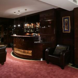 Utrzymane w klubowym klimacie wnętrze jest idealne do towarzyskich spotkań. Ścienna okładzina z lakierowanego drewna egzotycznego oraz zaprojektowany na planie koła bar, wykonany z tego samego materiału, nadają wnętrzu luksusowy charakter. Fot. Monika Filipiuk.