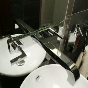 """Bateria umywalkowa """"Axor Citterio"""" Hansgrohe to model podtynkowy zamocowany na lustrze. Metaliczne listwy dekoracyjne pełnią rolę ramy lustra, zajmującego pas ściany od podłogi po sufit. Fot. Monika Filipiuk."""