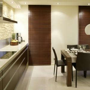 Okna w kuchni osłaniają drewniane żaluzje w kolorze zbliżonym do mebli. Rozciągnięte na całej wysokości wnętrza są także  intrygującym akcentem. Fot. Bartosz Jarosz.