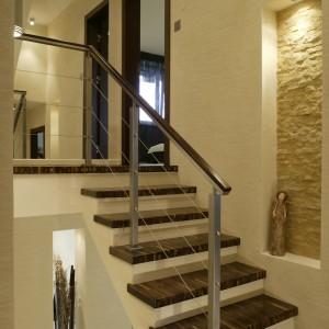 Widoczne z salonu schody są proste i eleganckie. Na szkielecie w kolorze ścian, zamontowano drewniane stopnie (dąb czarny), co nadaje konstrukcji delikatności i lekkości. Fot. Bartosz Jarosz.