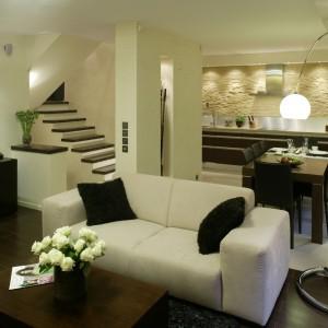 Salon otwiera się na strefę jadalnianą oraz kuchnię. Te trzy strefy tworzą jednolitą, zwartą całość, dzięki zastosowaniu nawiązujących do siebie kolorem drewna (ciemny dąb) mebli. Fot. Bartosz Jarosz.