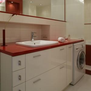 Blat z czerwonego, połyskliwego MDF-u stanowi nie tylko zwieńczenie podumywalkowej szafki, ale też przesłania od góry pralkę. Bryłę mebla wypełniają szafki i szuflady o różnym przeznaczeniu. Fot. Monika Filipiuk.