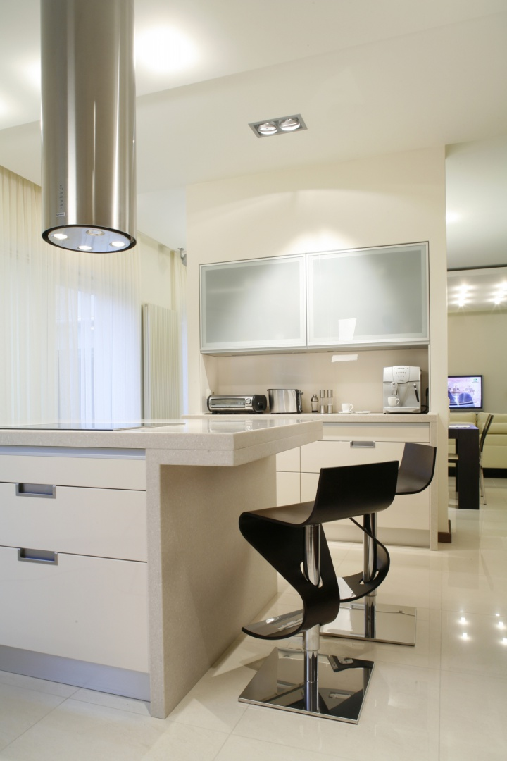 Wielofunkcyjna, wykonana z corianu wyspa, służąca jako miejsce gotowania, zmywania oraz bar, to najważniejszy, organizujący przestrzeń, element kuchni. Fot. Bartosz Jarosz.