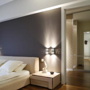 Dzięki umieszczeniu za ścianą pojemnego pokoju garderobianego, sypialnię można było urządzić nowocześnie i oszczędnie. Brak drzwi ułatwia komunikację między pokojami. Fot. Bartosz Jarosz.