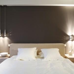 Na tle ściany, pomalowanej na odcień chłodnego brązu, stanęły meble: proste, minimalistyczne szafki fornirowane dębem bielonym oraz duże, tapicerowane łóżko z szerokim zagłówkiem. Za ścianą znajduje się garderoba o nieco asymetrycznym kształcie. Fot. Bartosz Jarosz.