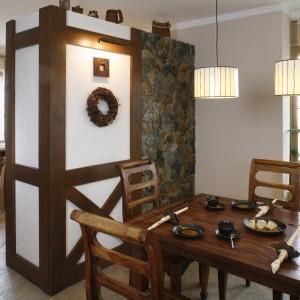 Jadalnię i kuchnię dzieli ścianka stylizowana na mur pruski i kamienny. Komplet jadalniany to meble z palisandru kupione w sklepie Almi Decor. Fot. Monika Filipiuk.