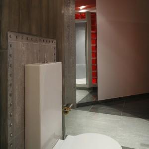 Półokrągła, betonowa ściana wygląda jakby pozostawiono ją w stanie surowym. Dzieje się tak za sprawą widocznych śladów po deskach szalunku. Jej dekoracyjność jest godną konkurencją dla czerwonych akcentów. Fot. Monika Filipiuk.