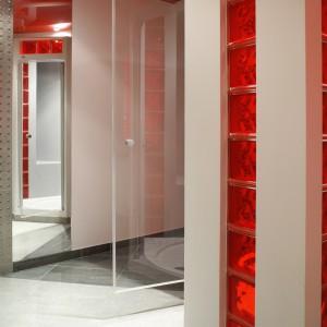Kabina prysznicowa ma kształt nieregularnego sześciokąta. Zbudowana z przezroczystych tafli szkła i czerwonych pustaków szklanych stapia się w jedną całość z pozostałymi elementami łazienki. Fot. Monika Filipiuk.