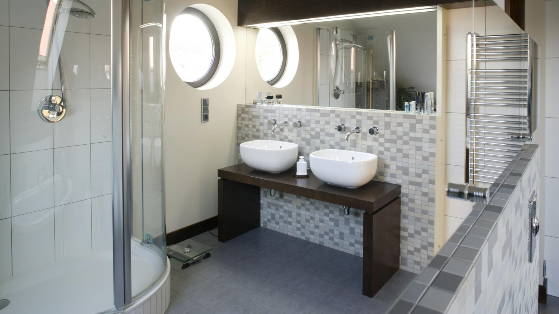 Długie rzędy szafek z ciemnego drewna nad umywalkowym lustrem oraz z lustrzanymi frontami sedesem i bidetem pozwalają uniknąć nagromadzenia kosmetyków i toaletowych akcesoriów w eksponowanych miejscach. Fot. Bartosz Jarosz.