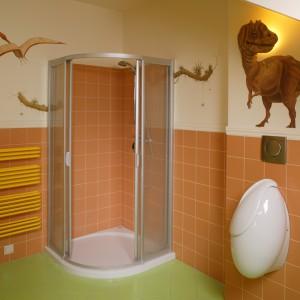 Kabinę prysznicową i strefę higieniczną – z pisuarem i sedesem – oświetla lampa ukryta za głową dinozaura, wykonaną z masy plastycznej. Jego tułów został namalowany na ścianie. Fot. Bartosz Jarosz.