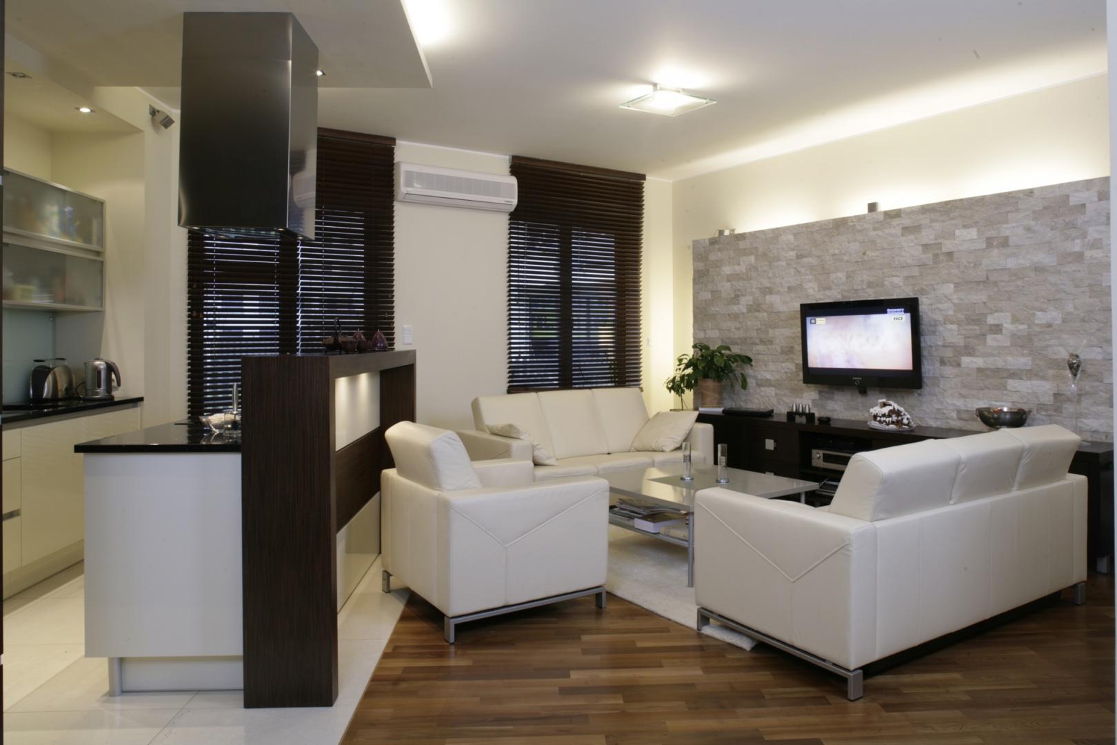 Salonowo–kuchenna przestrzeń jest jednorodna pod względem stylu i zastosowanych barw. Dominują tu minimalistyczne formy o eleganckich liniach. Fot. Monika Filipiuk.