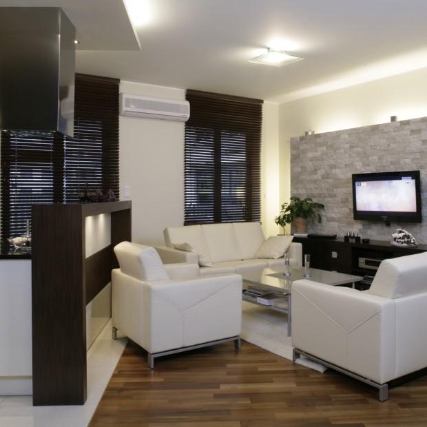 Wnętrze: kamień na ścianie i beżowe meble wypoczynkowe