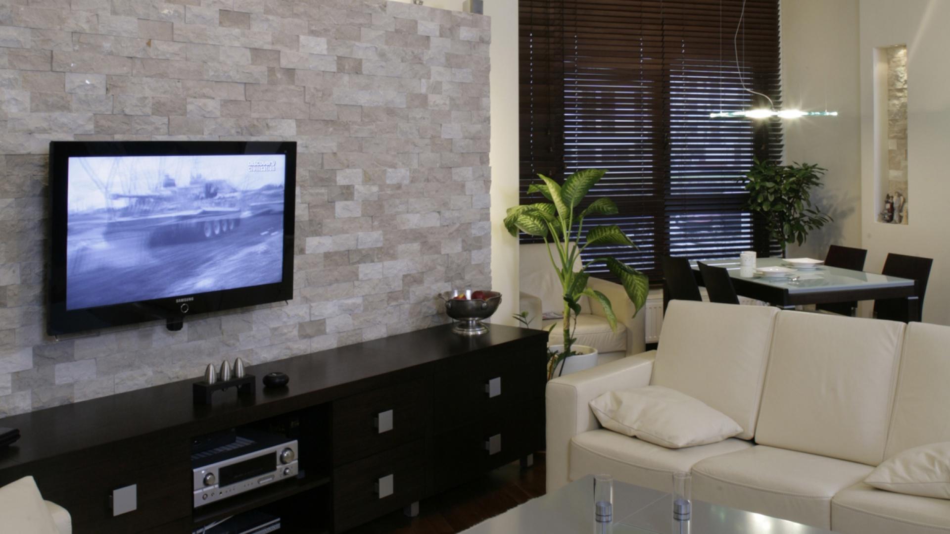Efektownie podświetlona kamienna ściana okryta została łupanką marmurową (Breccia sardo). To zarazem główna atrakcja salonowego wnętrza, służąca za tło płaskiego ekranu telewizora i niskiej, podłużnej szafki RTV. Fot. Monika Filipiuk.