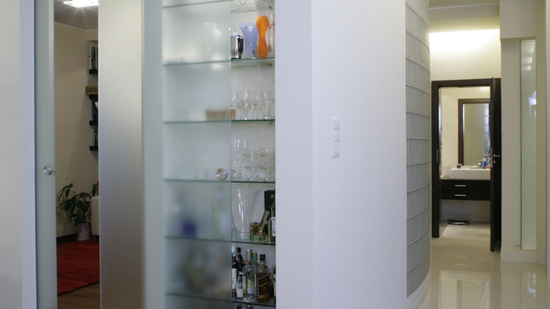 Dekoracyjna ścianka z luksferami została poprowadzona po łuku. Za szklanym okienkiem znajduje się garderoba gospodyni. Od strony salonu ścianka przechodzi w konstrukcję, w której zamontowano dwie tafle suwanych drzwi. Fot. Monika Filipiuk.