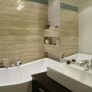Łazienka przy sypialni została urządzona w tym samym stylu co gościnne WC. Pod trawertynową ścianą umieszczono wannę o oryginalnym, geometrycznym kształcie (jej środkowa część jest nieco obniżona). Fot. Monika Filipiuk.