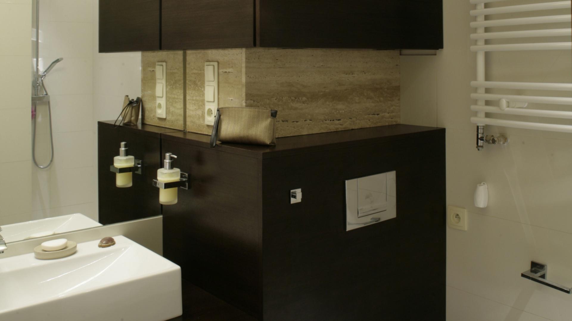 Przed prostokątną bryłą umywalki ulokowano szafki w fornirze wenge. Z tego samego materiału powstała też obudowa ściany w strefie sanitarnej. Wnęka, wyłożona trawertynem, nawiązuje do ogólnego charakteru wnętrza. Fot. Monika Filipiuk.
