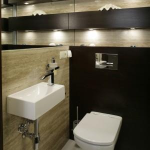 Gościnna toaleta została urządzona niezwykle elegancko. Część ściany oraz dekoracyjne wnęki zostały wyłożone trawertynowymi płytami Clasico, z wyrazistym piaskowym wzorem. Fot. Monika Filipiuk.