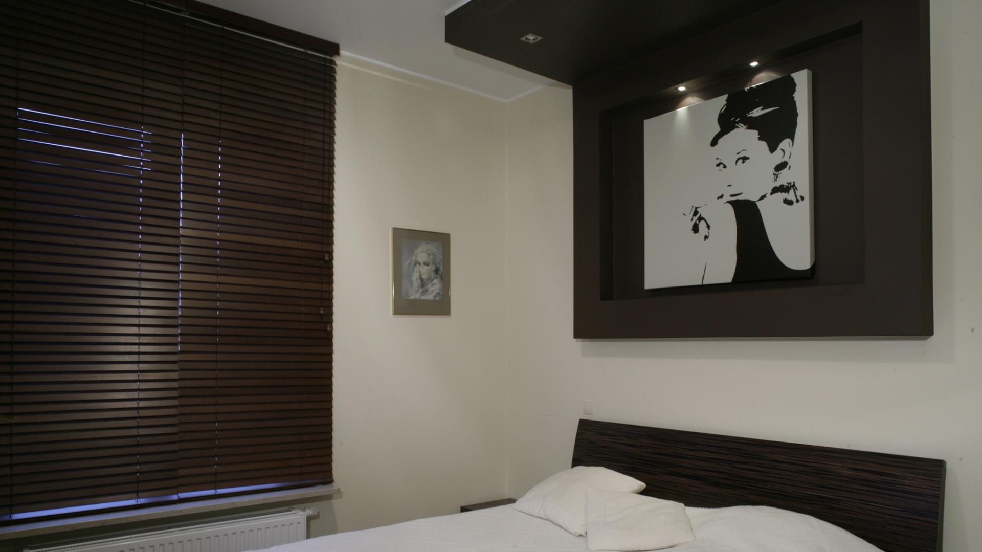 Skromną, choć niezwykle kobiecą, przestrzeń sypialni wypełnia ogromne łóżko fornirowane hebanem, z mocnym czarno-brązowym wzorem. Na ścianie zawieszono konstrukcję z suchego tynku. Fot. Monika Filipiuk.