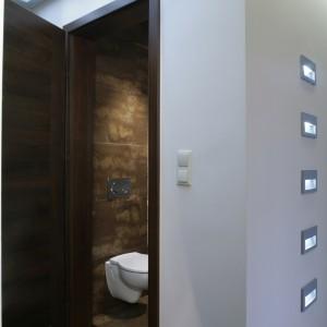Toaleta, znajdująca się tuż przy wejściu do domu, jest wyeksponowana za pomocą oświetlenia. W suficie, nad drzwiami, zainstalowano świetliki – szkło w formach aluminiowych (na 3 świetlówki). Fot. Monika Filipiuk.
