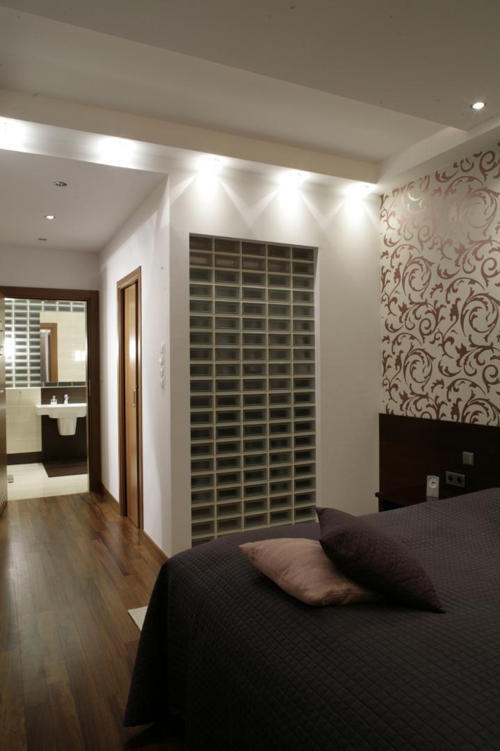 Wejście do łazienki znajduje się w obrębie małżeńskiej sypialni. Motyw obecnych nad umywalką pustaków szklanych powtarza się na ścianie między sypialnią i holem. Fot. Monika Filipiuk.