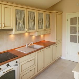 Kuchnia jest dużym, osobnym pomieszczeniem z rodzinnym stołem. Zabudowę rozpoczyna przy drzwiach wysoka lodówka typu kombi. Fot. Bartosz Jarosz.