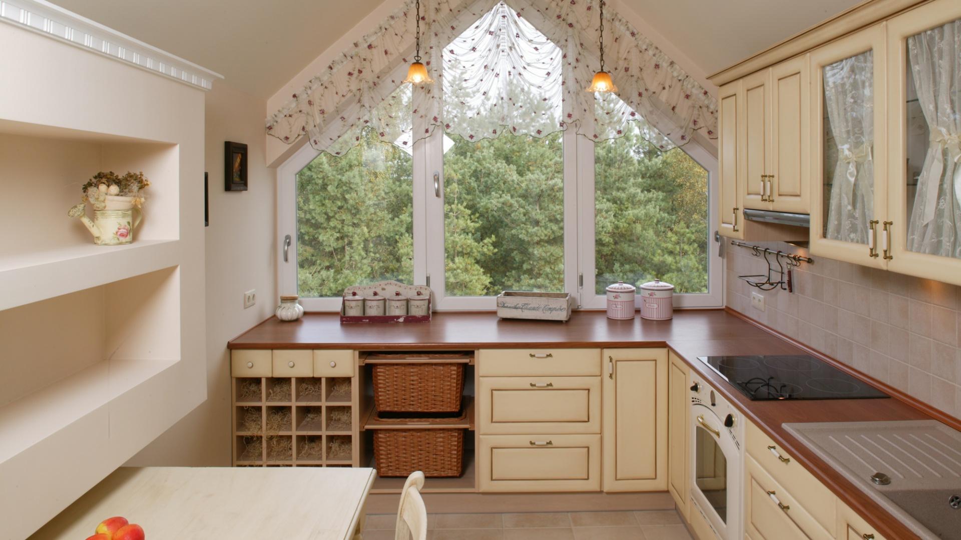 Okno zajmujące całą ścianę jest wyjątkową ozdobą jasnej kuchni urządzonej w stylu anglosaskim. Panuje tu nastrój spokoju, przytulności, rodzinnego ciepła. Fot. Bartosz Jarosz.