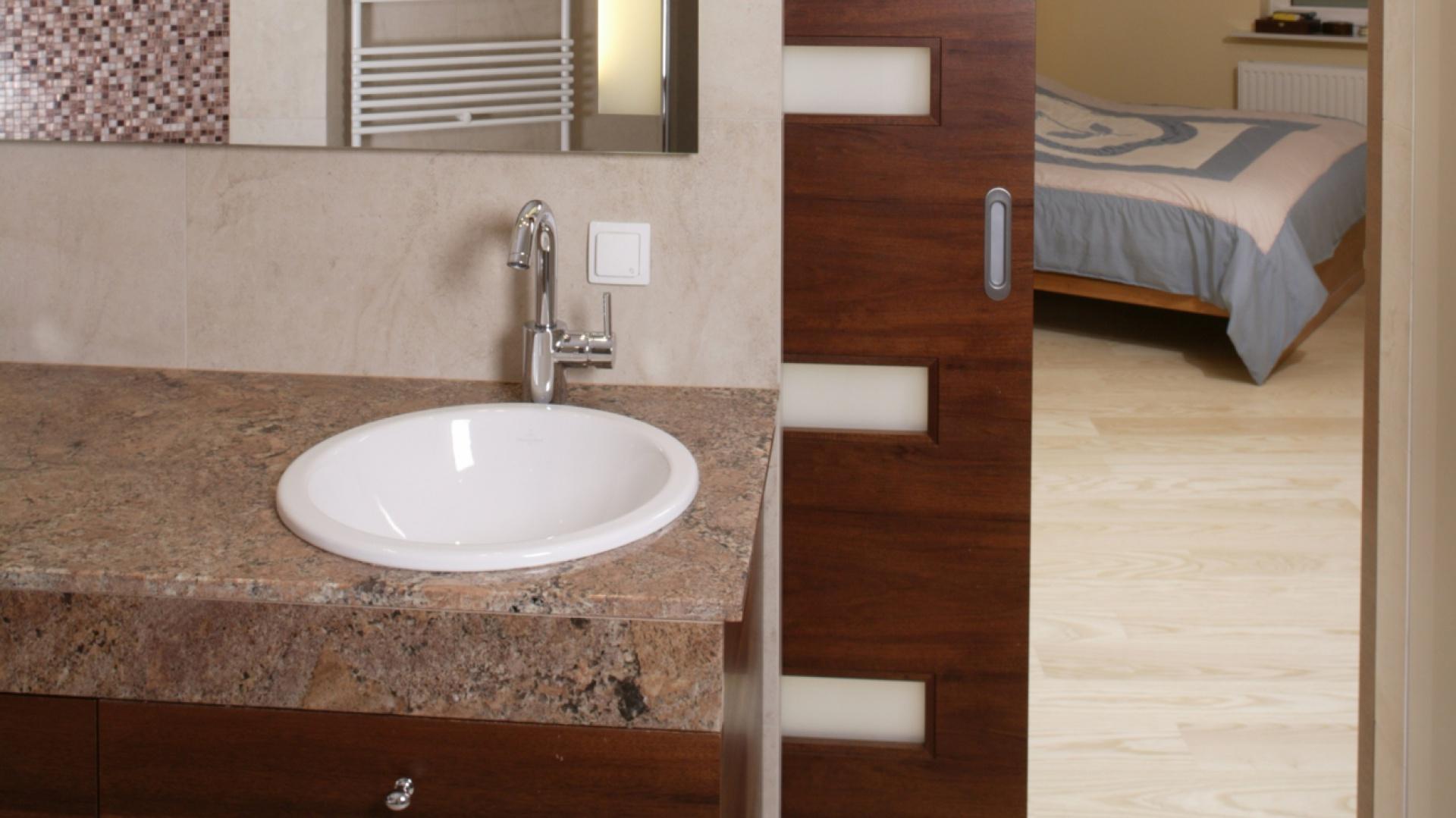 Łazienkę i sypialnię dzielą przesuwne, chowane w ścianie drzwi. Po ich otwarciu, oba pomieszczenia tworzą jedną, stylistycznie spójną przestrzeń. Fot. Bartosz Jarosz.