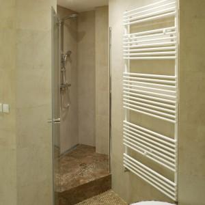 Nieregularny kształt kabiny jest spowodowany wydzieleniem za jej ścianą pomieszczenia na pralnię. Brodzik został skrojony na miarę z granitu. Odpływ wody umieszczono wzdłuż ściany. Fot. Bartosz Jarosz.