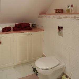 Obudowa podtynkowego systemu spłukującego została przedłużona na całą ścianę i tworzy półkę zwieńczoną blatem w różowym odcieniu. Fot. Monika Filipiuk.